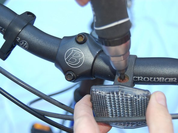 Image 1/1: Using a Phillips-head screwdriver, tighten the bracket until it is snug around the handlebar.