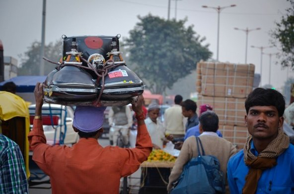 A man carries a pair of CRTs on his head at Lajpat Rai