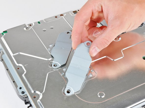 Image 1/1: Remove the two heat sink clamps from the bottom of the motherboard assembly.