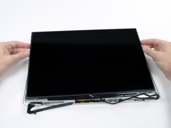 Pull the LCD toward the top of the display panel, freeing the screw tabs from underneath the rear display bezel.