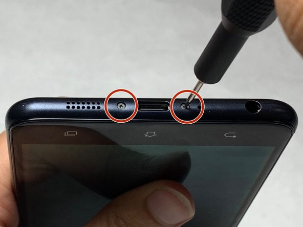 Remove the 3.5 mm screws on both sides of the charging port, at the bottom of the phone, using the T2 screwdriver.