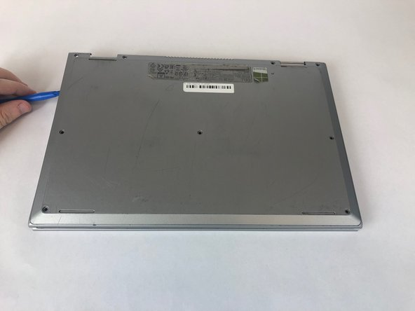 Use a plastic opening tool to remove the cover from the computer.