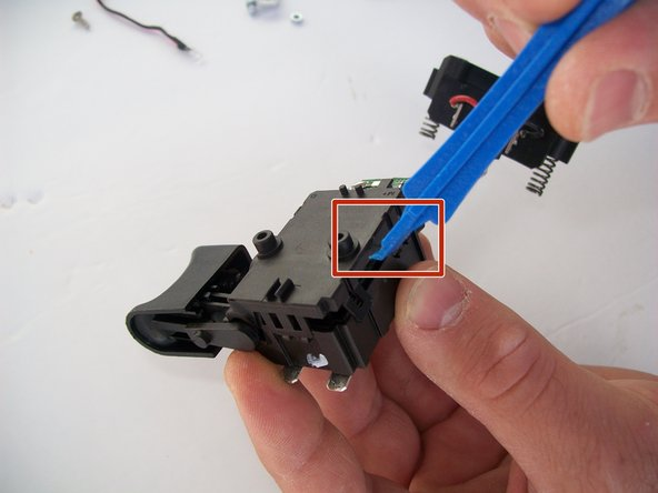 Use a plastic pry tool to gently pry open the trigger chip compartment.