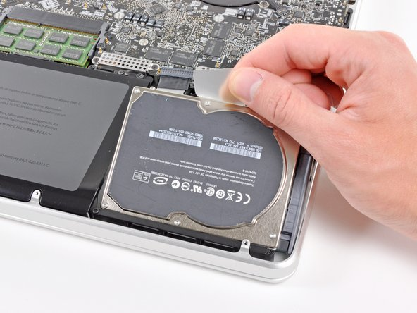 Use the hard drive's pull tab to lift it out of the upper case.