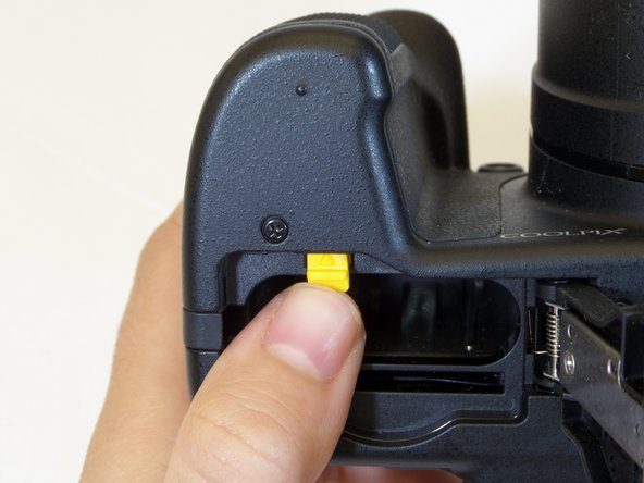 Once the battery cover is open, push the solid yellow tab in the direction of the arrow. This will then eject the battery out of the camera.