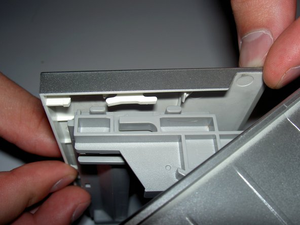 Note the position of the tabs in these pictures. Once the casing has slid forward, it should come loose. Place it aside.
