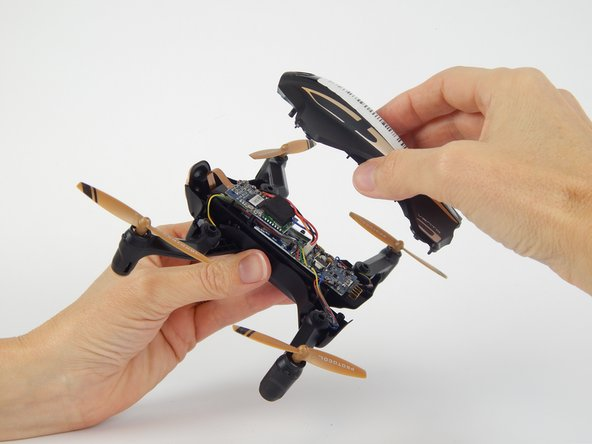 Flip the drone over and lift off the top plastic shell of the drone.