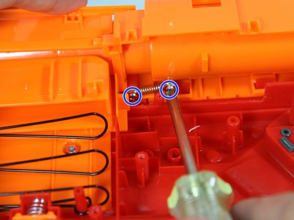 Locate the screws on the return spring. Using a counterclockwise rotation, remove both of the screws.