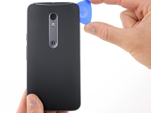 Slide the opening pick along the edge of the phone to slice through the back cover adhesive.