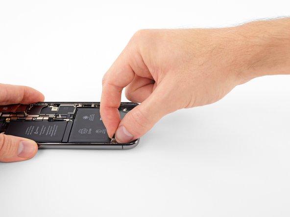 Saisissez la languette adhésive à gauche ou à droite de la batterie, puis tirez dessus, depuis la batterie vers le bas de l'iPhone.