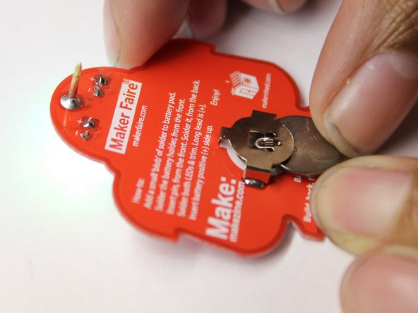 Slide the battery into the battery holder on the badge. One side of the battery has text -- this side should be facing up (away from the PCB) as illustrated.