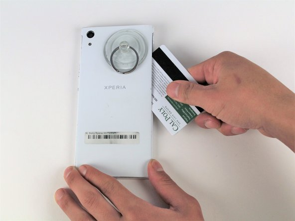 Slide your plastic card along the side of your phone to loosen the adhesive.