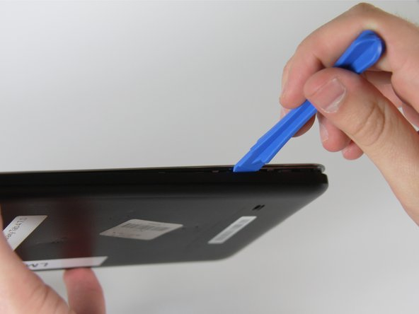 Image 1/2: Slide the opening tool around the edges of the device to disconnect the back panel from the frame.