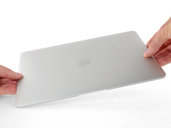 While holding the lower case in place, carefully flip the MacBook over so the Apple logo faces up.