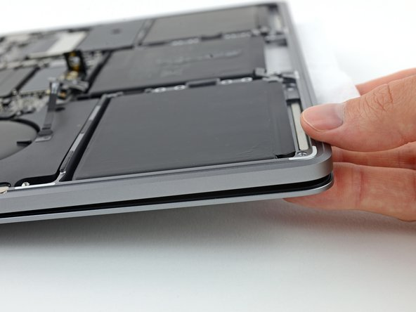 Tip the front edge of your MacBook Pro up at a slight angle so that the liquid adhesive remover flows underneath the battery cell.