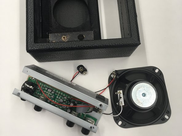 Begin by unscrewing the four 12 mm screws that are holding the subwoofer firm with a Phillips #00 screwdriver.