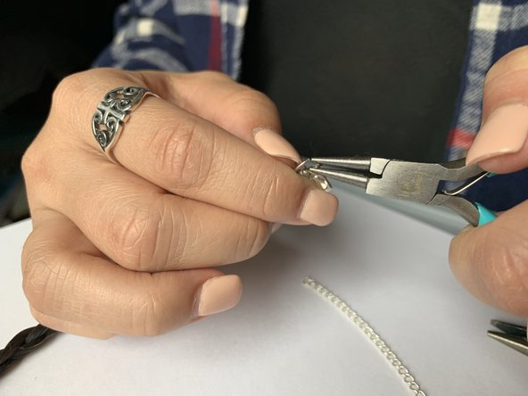 Begin to pull the sides of the jump ring together using the pliers.