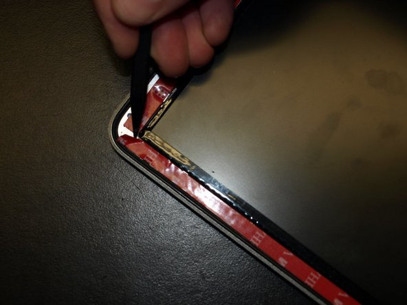 On the upper corner of the adhesive on the left side of the display assembly.