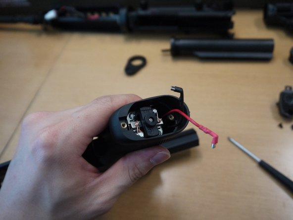 Arrange the wires so that both are against the rear of the pistol grip. Place the motor in the pistol grip, making sure that it slides in freely and bounces back from spring tension after you push down on it.