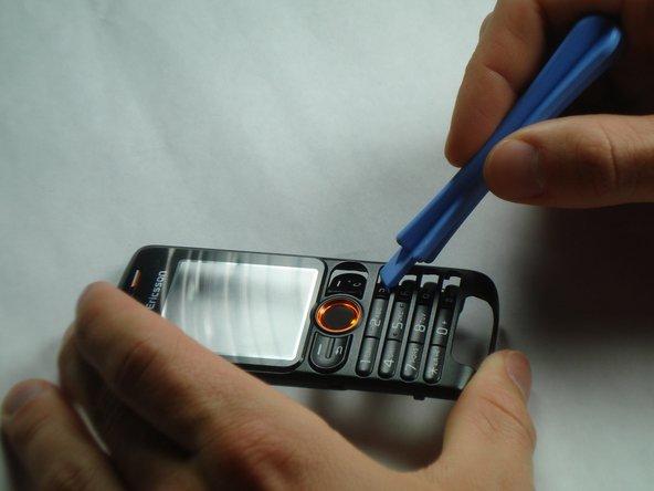 À l'aide de l'outil d'ouverture en plastique, appuyez sur n'importe où sur le clavier pour le séparer de l'étui avant.