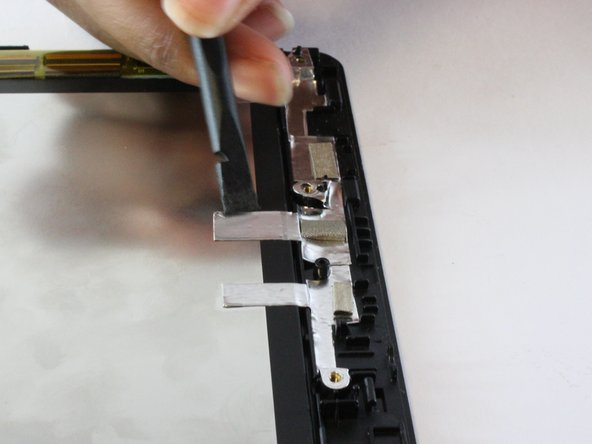 Peel the silver tape on the side of the tablet using the nylon spudger. Do not completely remove the tape.