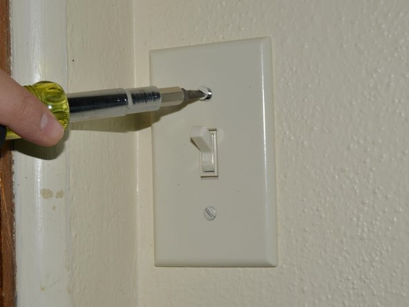 "Remove the face-plate from the light switch by unscrewing the two 7.9mm oval head slotted screws with the 3/16"" slotted screwdriver until the plate comes away freely."