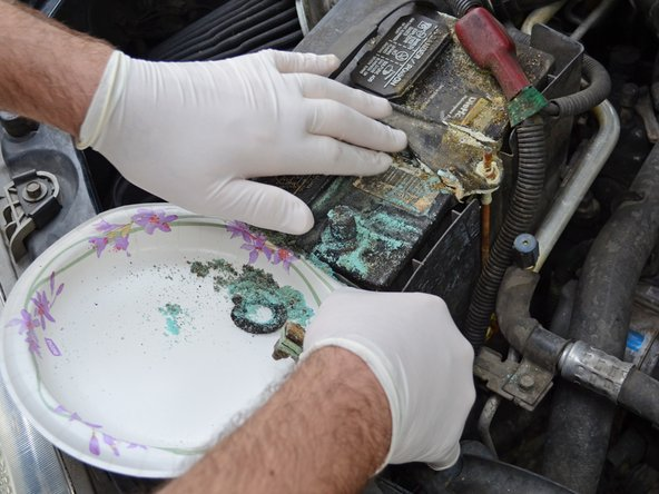 You may want to avoid getting the corrosion all over the inside of the engine bay. Sweeping the corrosion onto a paper plate or rag is a simple way to get the corrosion out of the engine bay without making a mess.