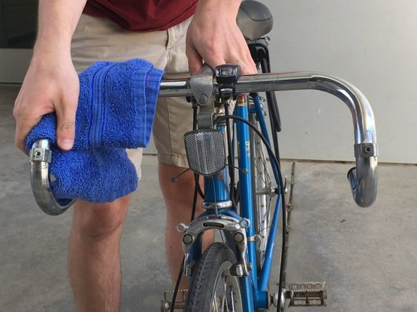 Pour some rubbing alcohol on the rag and clean any old adhesive residue off the handlebar.