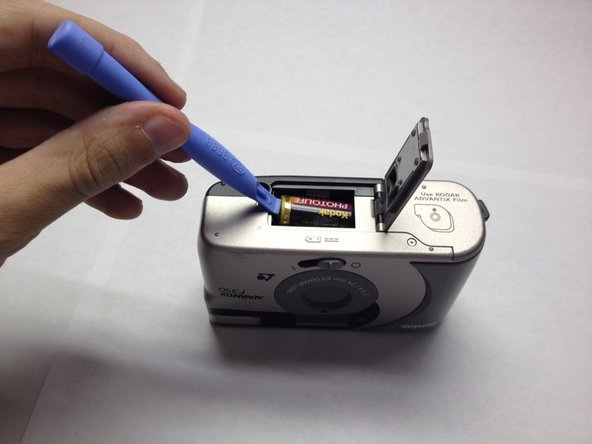 Use your plastic opening tool to slowly pry the battery from the camera case.