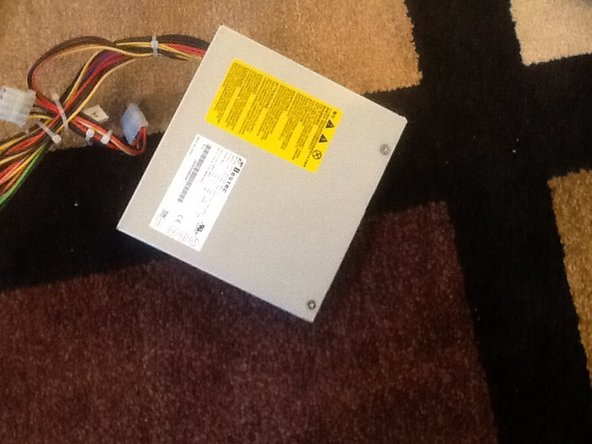 Remove the four screws from the power supply and then pull it back and out