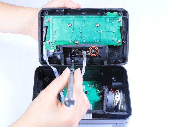 Using a Phillips #1 screwdriver, unscrew the two 7mm Phillips screws that attach the iPhone dock to the top cover of the clock.