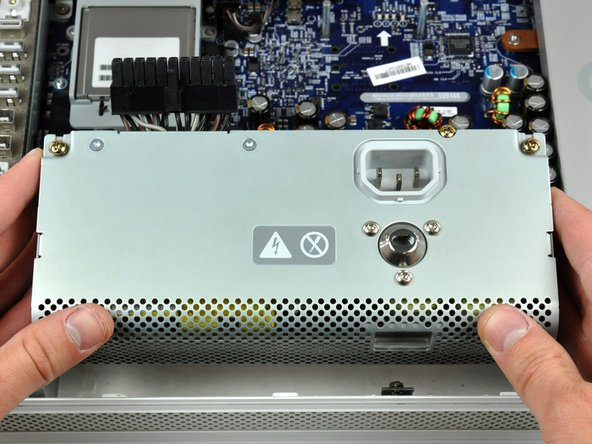 Grab the power supply from each side and rotate its top edge toward yourself until it clears the logic board.