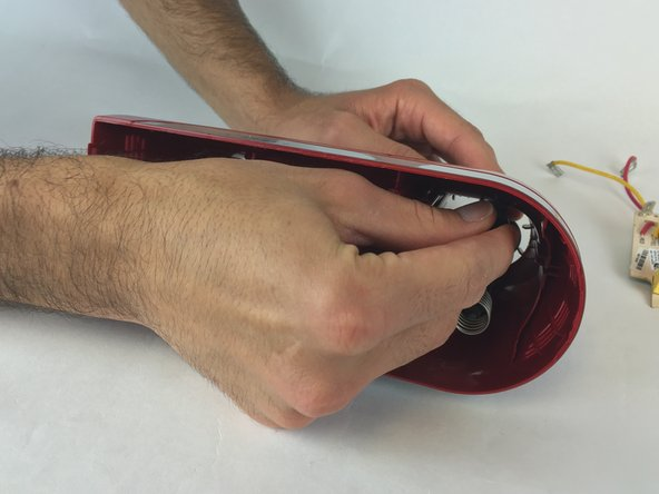 Image 1/2: Hold the eject button firmly while pulling out the spring.