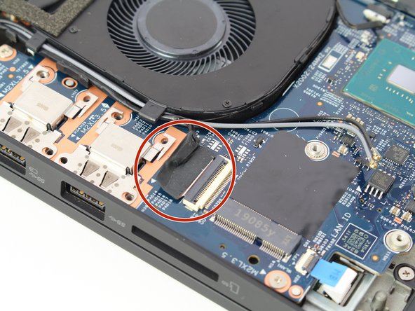Unlatch and remove the cable connecting to the frame of the fan by flipping the thin black tab up.