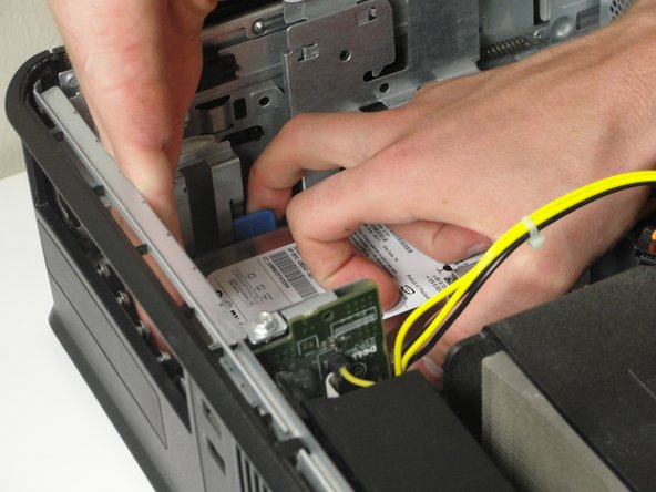 Push the large blue tab into the hard drive and push the hard drive away from the tower wall.