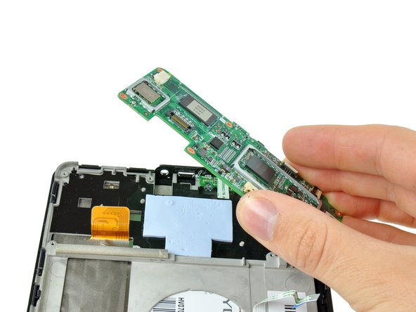 Image 3/3: Lift the motherboard out of the Kindle Fire, making sure that the power button cable from step 8 comes free from its connector.