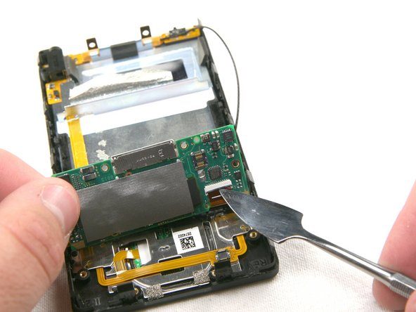 Carefully lift up the mother board located at the base of the Zune. Unclip the orange ribbon cable in the same manner as in the previous steps.