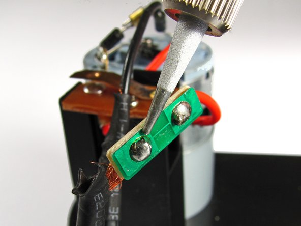 Using a soldering kit, remove the solder for the black power cord from the circuit board.