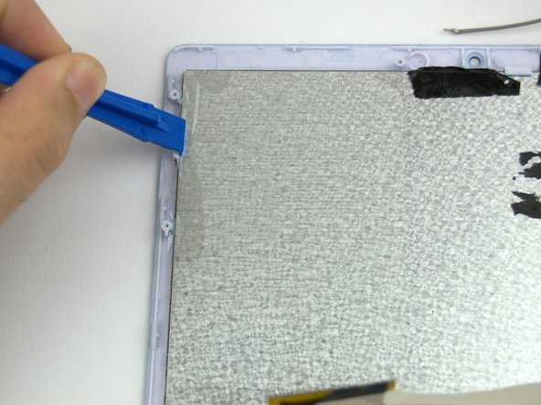 Image 2/3: Use a plastic spudger to separate the clips from the display.