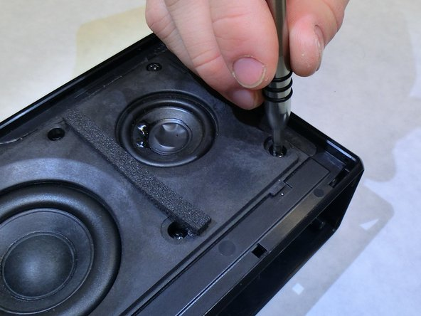 Locate the eight 8.9 mm screws on the face of the speaker assembly and remove them using a Phillips head #2 screwdriver.