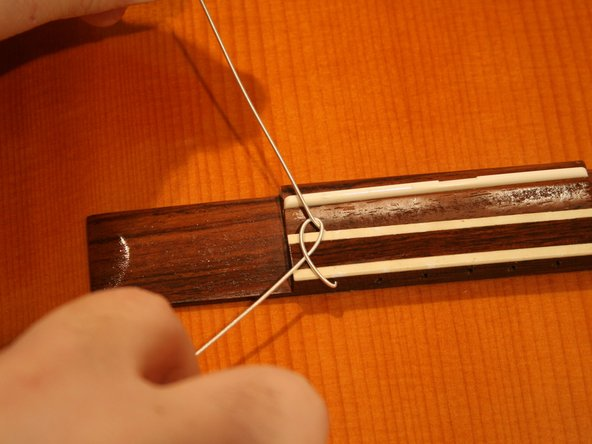 Insert the thick end of the string into the top of the bridge and thread it through until about 3 to 4 inches of the string sticks out of the bottom.