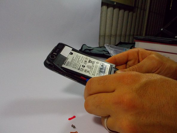 Image 2/3: Once the battery is loose, carefully lift from the bottom edge and remove the battery.