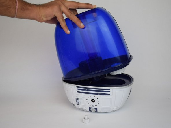 Remove the blue water tank of the humidifier by pulling upwards.