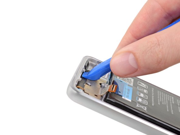 Place the flat end of an opening tool against the lower edge of the inside of the phone below the battery, as shown in the first photo.