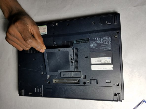 In the center of the bottom of the laptop, there is a panel with two screws. Using the JIS #1 screw head unscrew both.