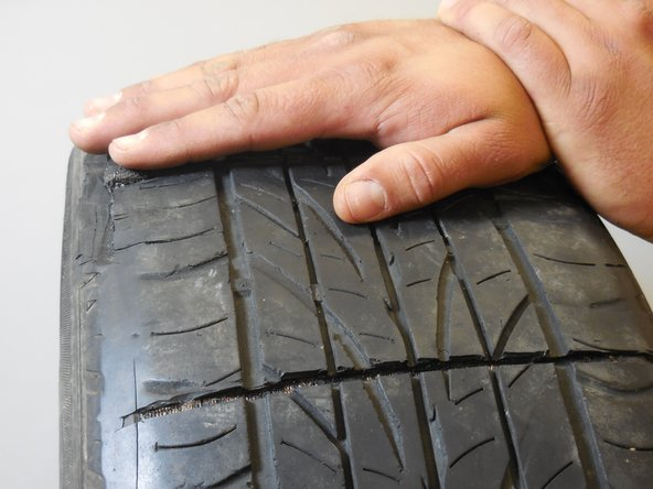 Cut across the tire using a knife creating a groove approximately the width of the tread.