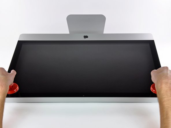 Image 1/3: Pull the glass panel away from the lower edge of the iMac and carefully set it aside.