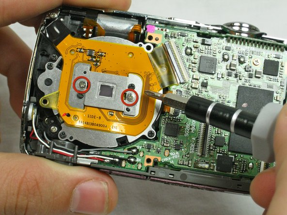 Remove the two 3.1 mm screws on the orange rectangular plate over the lens.