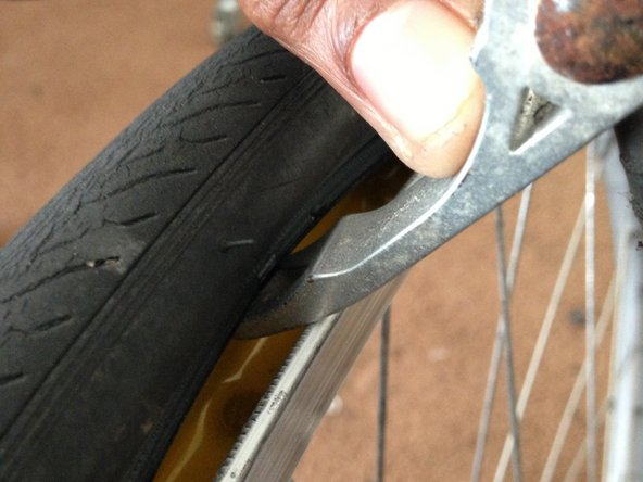 Image 1/3: Once firmly in place, push the tire tool down towards the ground in order to create spacing between the tire and the rim.