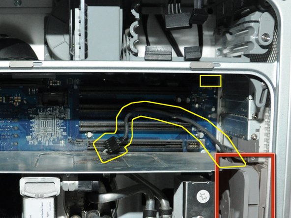 Image 1/1: Unplug the fan's power cable from the upper rightmost corner of the motherboard (connection J45). If there is a video card in place, carefully pull the cable plug down between the back edge of the video card and the motherboard. Note,  the photo shows the unplugged cable and the area it plugs into outlined in yellow. No video card is shown in this photo.